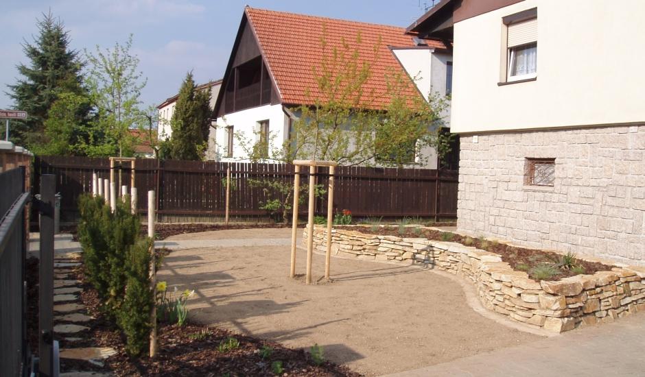 Předzahrádka u rodinného domu  se suchou zídkou, živým plotem z jehličnanů a s čerstvě vysetým trávníkem v Telči.