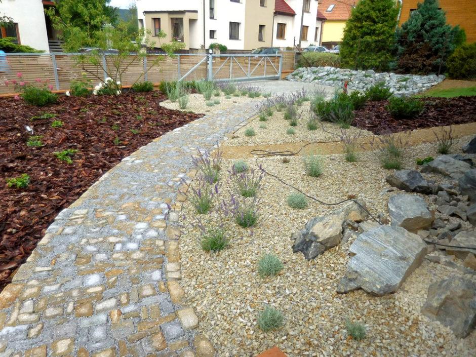 Nově založená zahrada těží z kontrastu keřové a trvalkové výsadby a kamenů.